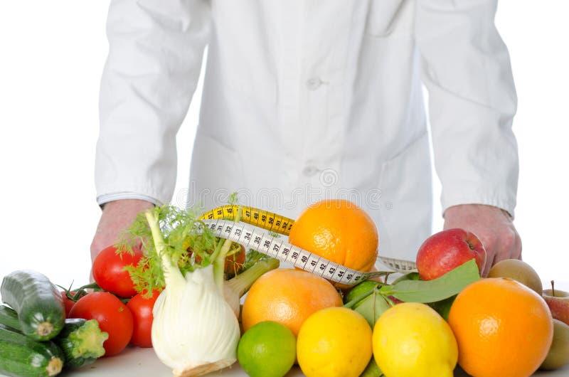 Nutricionista del doctor delante de las frutas y verduras fotografía de archivo