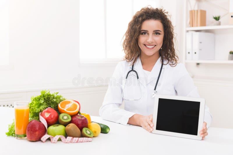 Nutricionista do doutor que guarda a tabuleta digital vazia, modelo imagem de stock royalty free