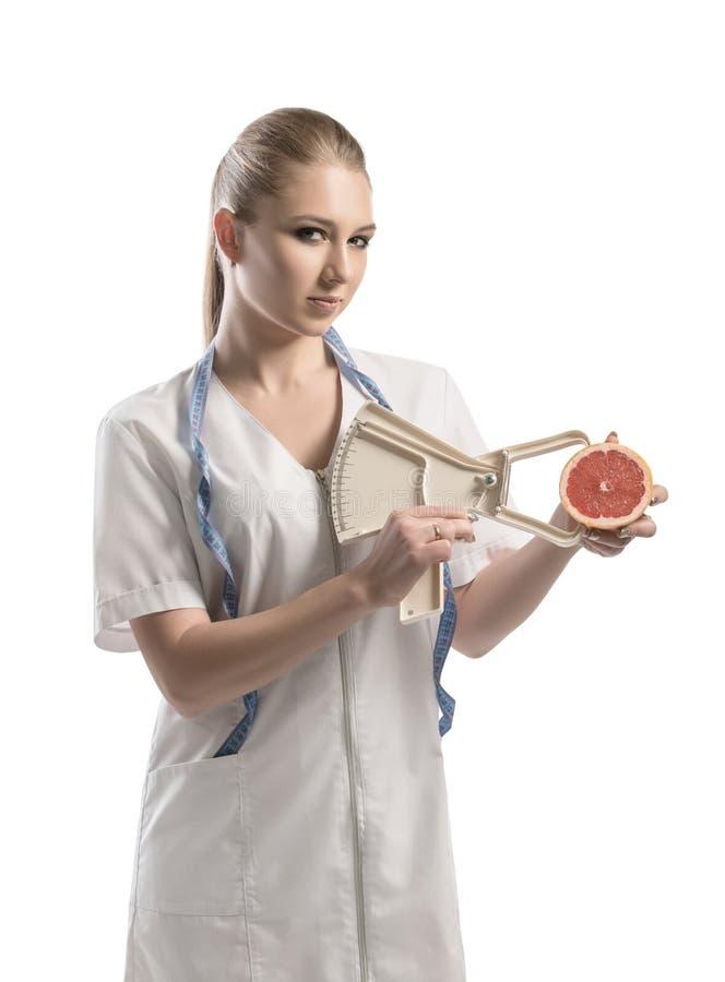 Nutricionista en uniforme del blanco con una cinta métrica imágenes de archivo libres de regalías