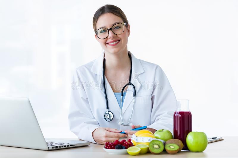 Nutricionista fêmea de sorriso dos jovens que olha a câmera na consulta fotos de stock