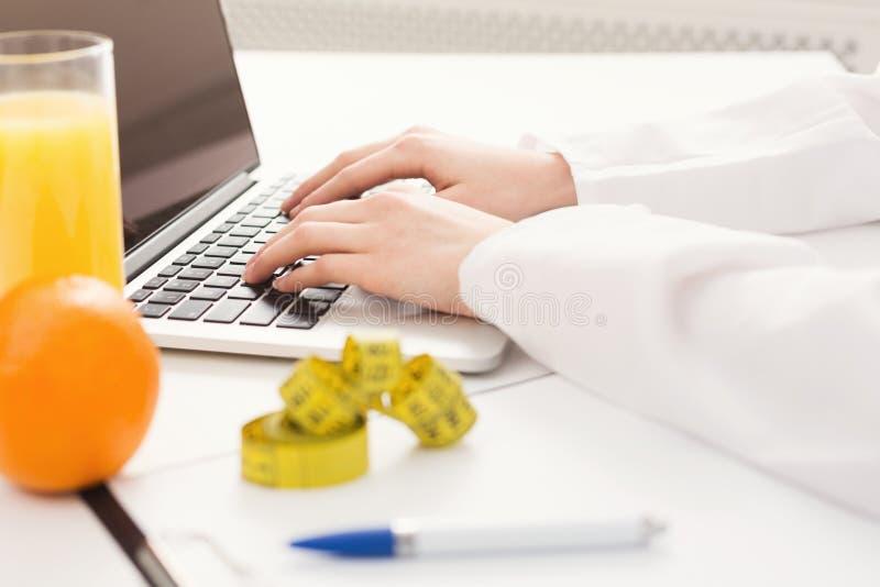 Nutricionista fêmea que trabalha no portátil imagem de stock royalty free
