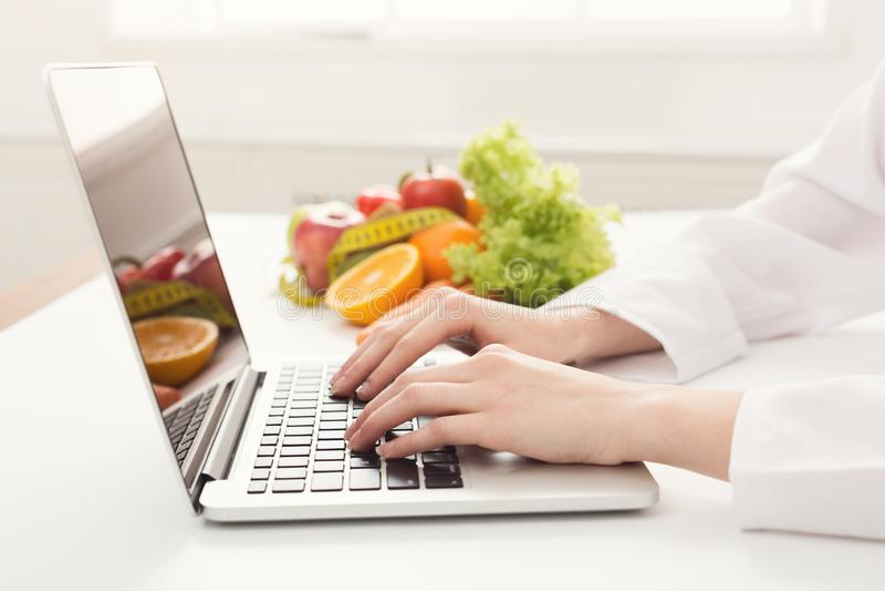 Nutricionista fêmea que trabalha no portátil imagens de stock royalty free