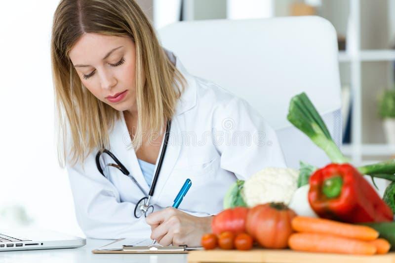 Nutricionista joven hermoso que trabaja en el escritorio y que escribe informes médicos sobre la fruta fresca en la consulta foto de archivo