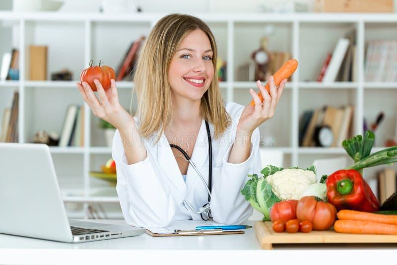 Nutricionista novo bonito que olha a câmera e que guarda legumes frescos na consulta fotografia de stock