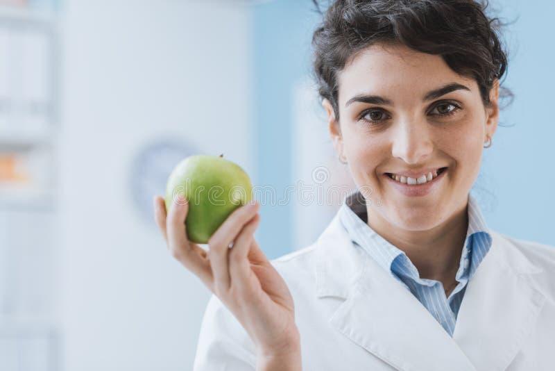 Nutricionista profesional que sostiene una manzana fresca imagen de archivo