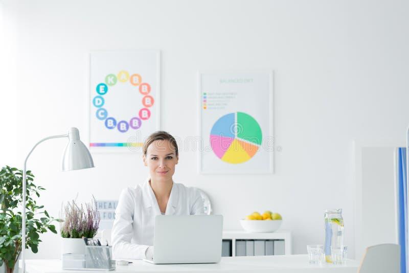 Nutricionista sonriente en la oficina blanca imágenes de archivo libres de regalías