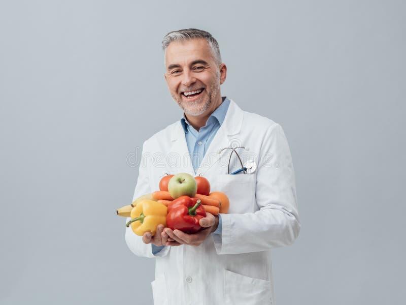 Nutricionista sonriente que sostiene verduras frescas y la fruta imagen de archivo libre de regalías