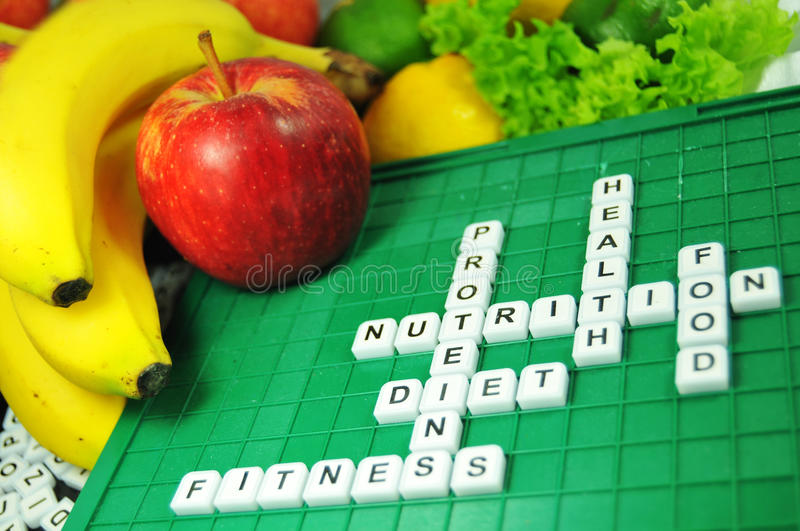Nutrition. Related words on a game board surrounded by fresh fruits and vegetables royalty free stock photography