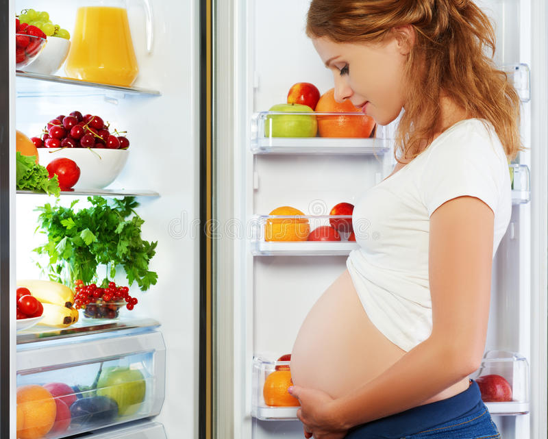 Nutrition and diet during pregnancy. Pregnant woman with fruits. Nutrition and diet during pregnancy. Pregnant woman standing near refrigerator with fruits and stock images