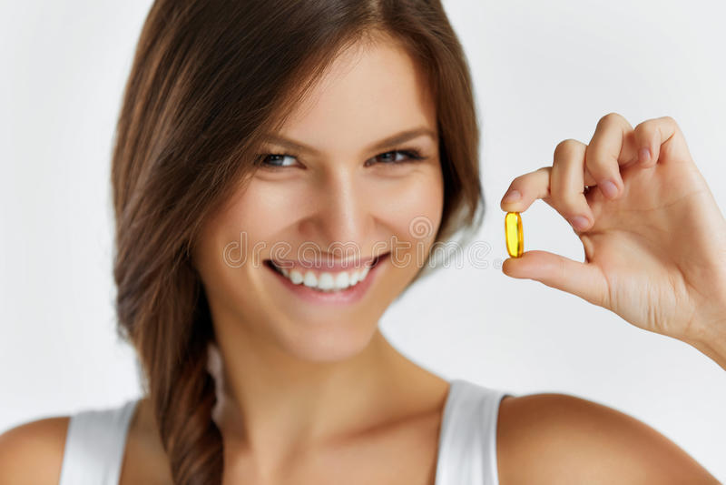 nutrition Estilo de vida saudável Mulher que guarda o comprimido com óleo de peixes O foto de stock
