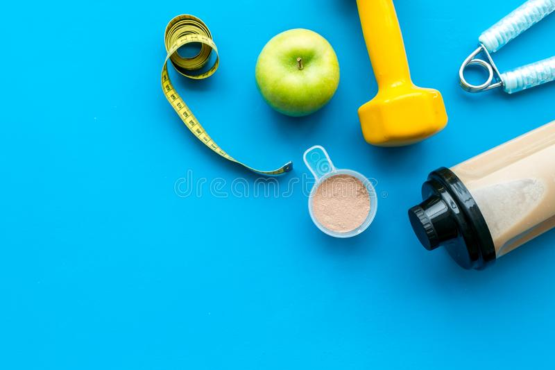 Nutrition for workout with protein cocktail and bars on blue background top view mockup royalty free stock images