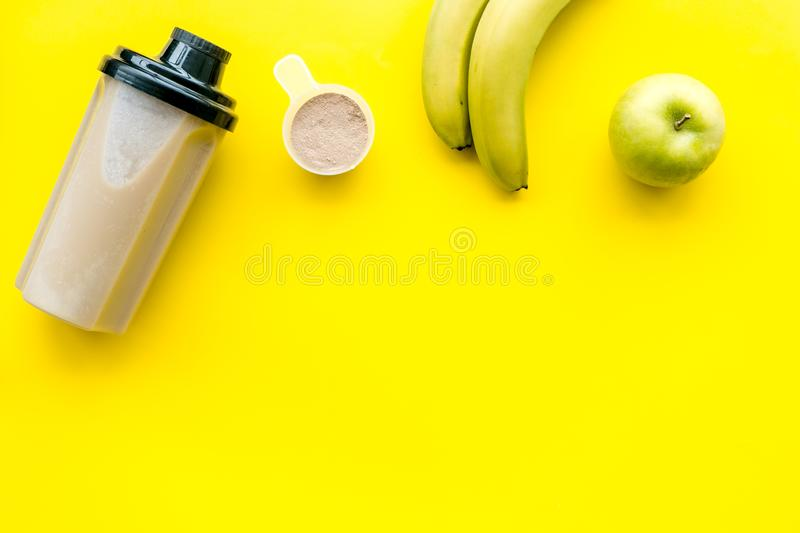 Nutrition for workout with protein cocktail and fruits on yellow background top view mockup royalty free stock images