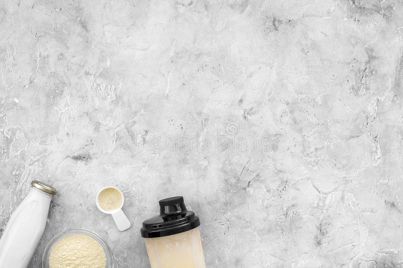 Nutrition for workout with protein cocktail, powder and milk on stone background top view mockup stock photos