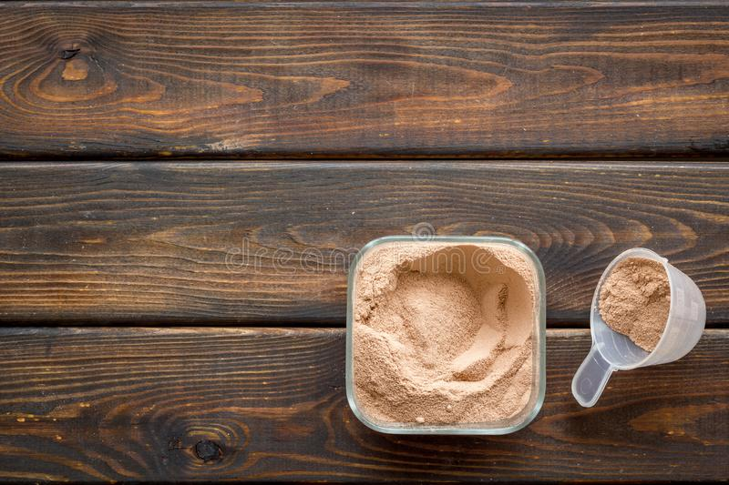 Nutrition for workout with protein cocktail powder on wooden background top view mockup stock image