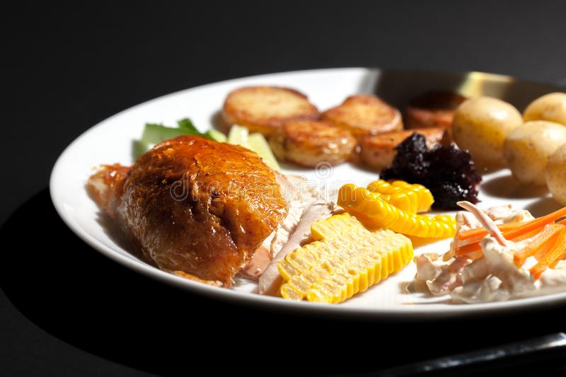 Nutritional chicken dinner meal. Low calorie healthy food on a p. Late. Roast chicken with sweetcorn, coleslaw, cranberry sauce, saute and boiled potatoes and stock photo
