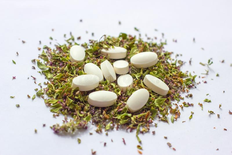 Nutritional supplements pills on dried herbs background. Alternative herbal medicine, naturopathy and homeopathy concept stock photography