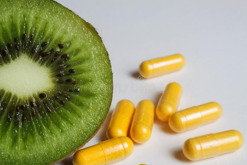 Nutritional vitamins supplement concept: Macro close up of isolated half sliced fresh ripe green kiwifruit with yellow capsules. Focus on kiwi stock photo