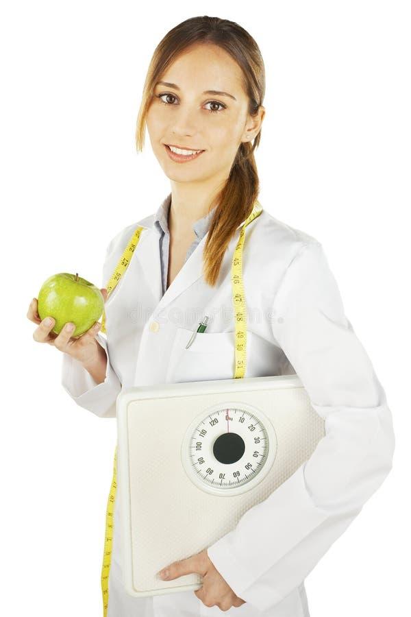 Nutritionist держа зеленый маштаб яблока и веса стоковые фотографии rf