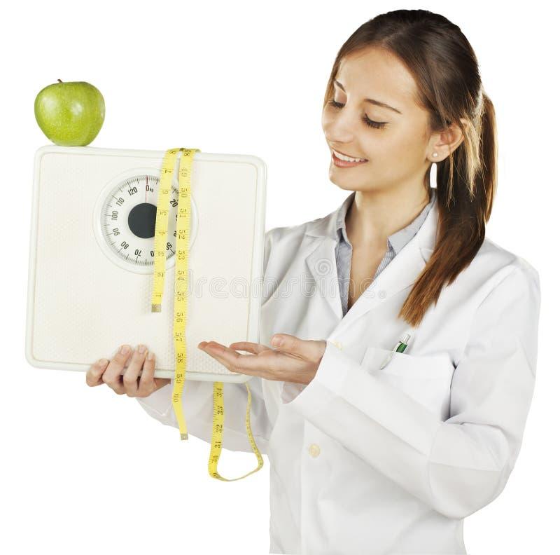 Nutritionist показывая маштаб веса и зеленое яблоко стоковая фотография rf