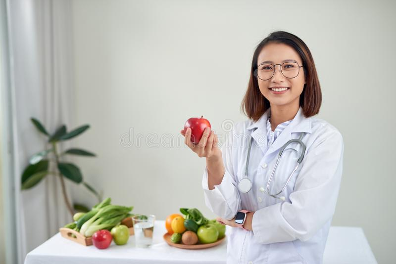 Nutritionist desk with healthy fruits, juice and measuring tape. Dietitian working on diet plan at office, smiling at camera. royalty free stock photography