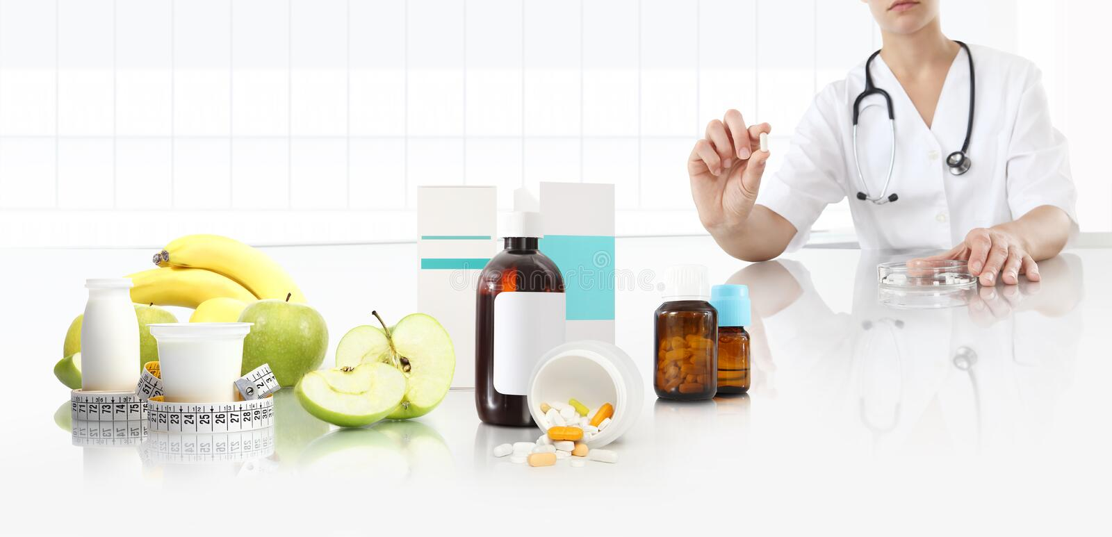 Nutritionist doctor shows the pill in his hand at the desk office with apple, fruits, yogurt, tape meter and supplements drugs, stock images