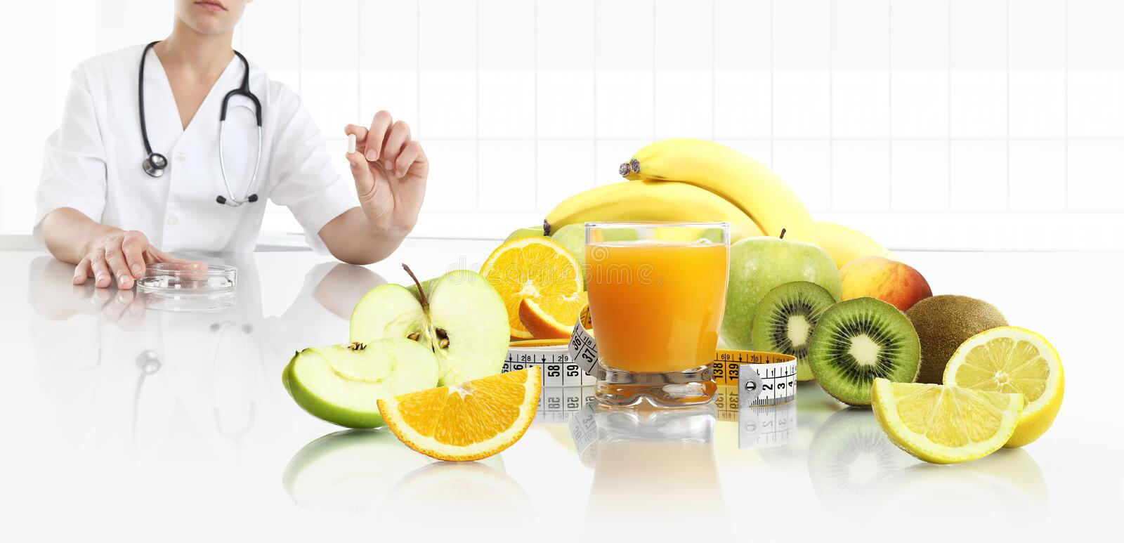 Nutritionist doctor shows the pill in his hand at the desk office with fruits, tape meter and orange juice, healthy and balanced stock photo