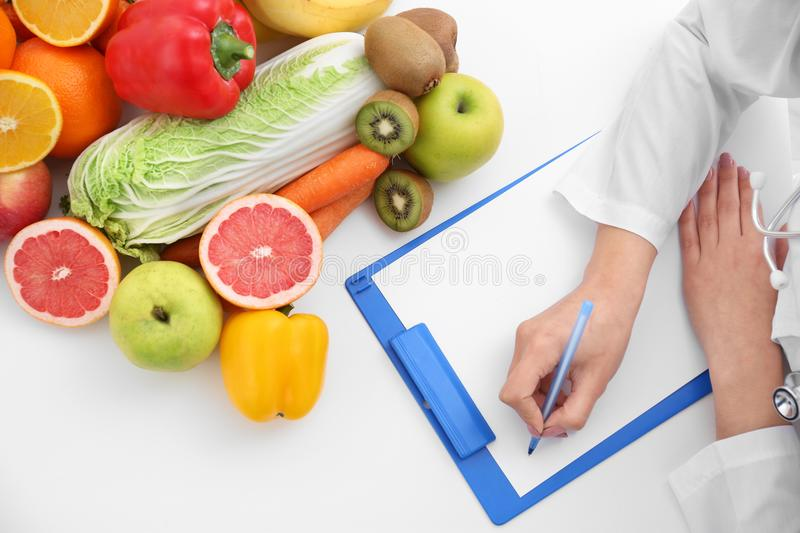 Nutritionist doctor writing diet plan stock photo
