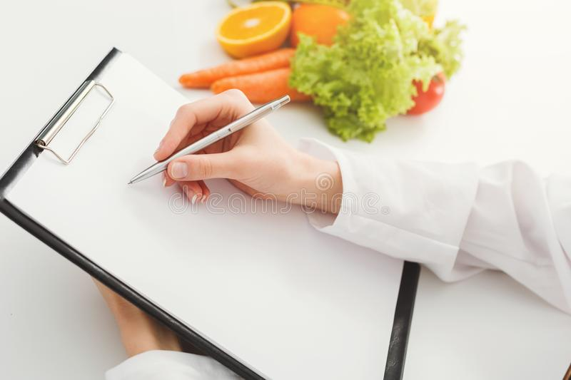 Nutritionist doctor writing diet plan on table royalty free stock image