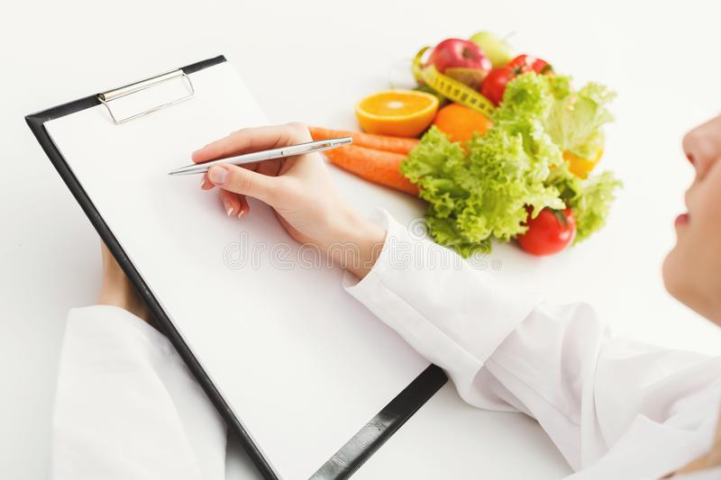 Nutritionist doctor writing diet plan on table royalty free stock photo