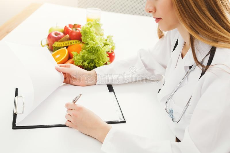 Nutritionist doctor writing diet plan on table. Unrecognizable dietitian making healthy eating menu, copy space for text. Right nutrition and slimming concept stock photography