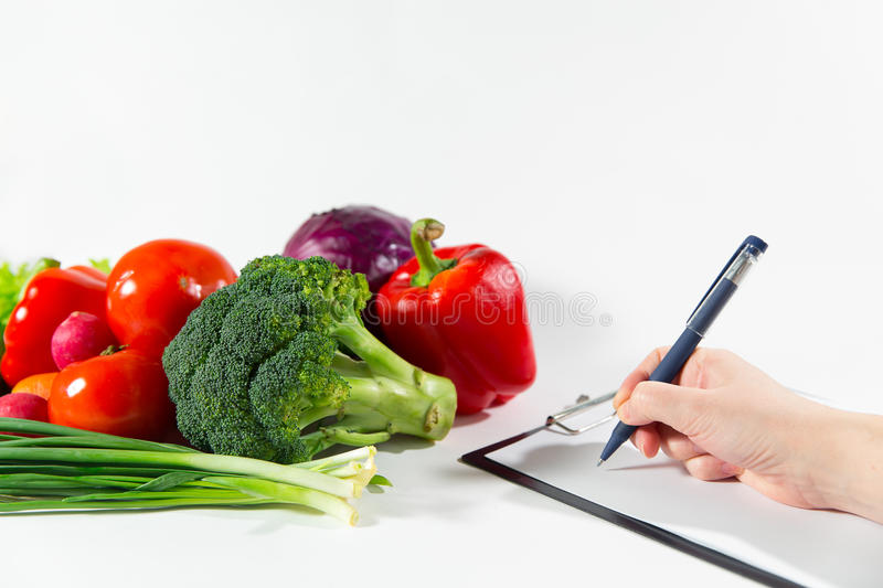 Nutritionist doctor writing vegetable diet plan royalty free stock photography