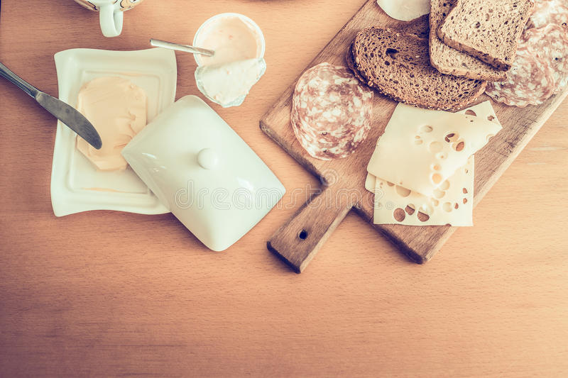 Nutritious breakfast, ingredients for making sandwiches with salami, butter and cheese, yogurt on a wooden table top view stock photography