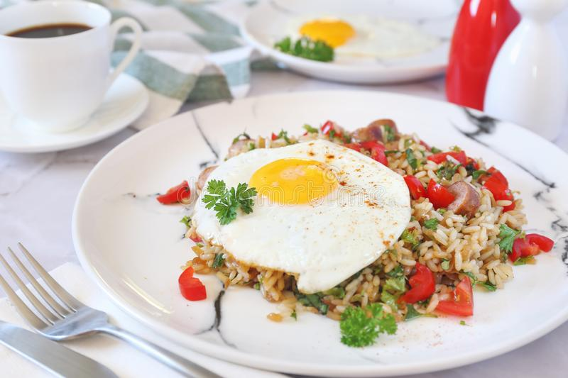 Spicy roast rice with red cherry tomatoes, sausages, fried eggs and cup of coffee for breakfast stock photography