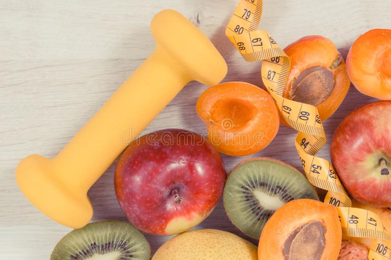 Nutritious fruits as healthy dessert containing natural vitamins, tape measure and dumbbell for fitness royalty free stock photo