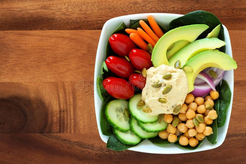 Nutritious lunch bowl with avocado, hummus and vegetables on wood. Nutritious lunch bowl with avocado, hummus and mixed vegetables, overhead view in square bowl stock images