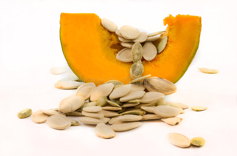 Nutritious pumpkin and seeds. Nutritious cut pumpkin with organic seeds on a white background royalty free stock photos