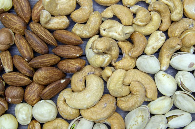 nuts almonds cashew hazelnuts scattered on a wooden table stock photo