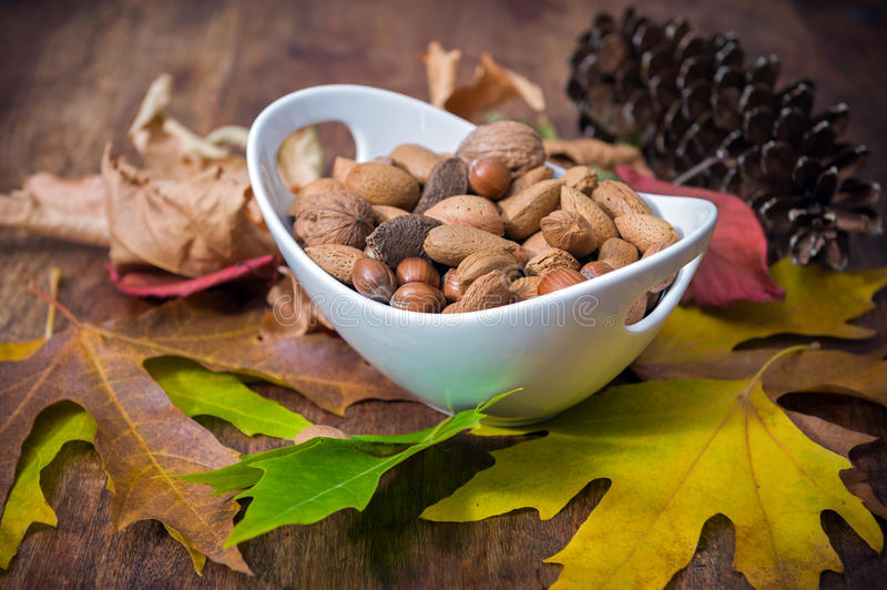 Nuts. Autumnal leaves and bowl of mixed nuts on a wooden table stock photo
