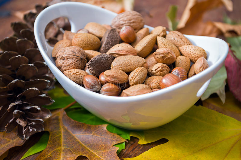 Nuts. Autumnal leaves and bowl of mixed nuts on a wooden table royalty free stock image