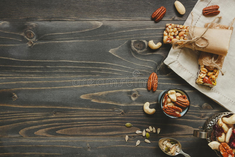 Nuts background. Healthy bars with nuts, seeds and dried fruits on the wooden table, with copy space royalty free stock photography