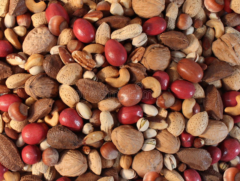 Nuts Background. With a mixed assortment of seeds and pecan with walnut brazil nut peanut,hazelnut pistachio almond and cashew as a healthy food symbol and royalty free stock photos