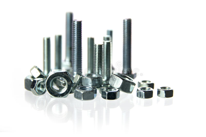 Nuts and bolts standing like a skyline with long reflections on. A white background, concept for construction, crafts and industry, closeup with selected focus stock photo