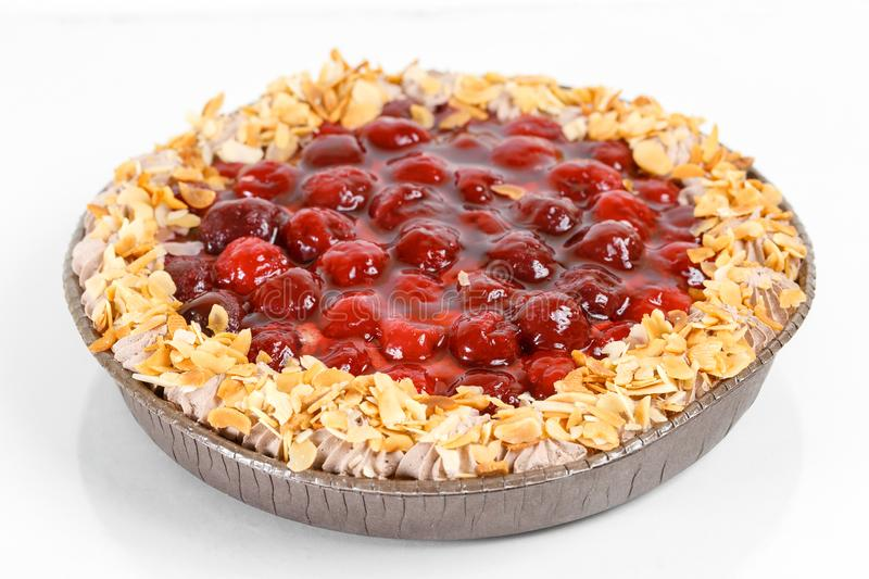 Nuts cake with cherry. Pie with almond and peanut on a Plate. Sweet food. Sweet dessert. Food background. Nuts cake with cherry. Pie with almond and peanut on a stock images