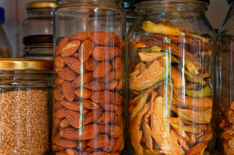 Nuts and dried apples in glass containers. Almonds and dried apple slices stored in glass jars, reducing the use of plastic stock photography