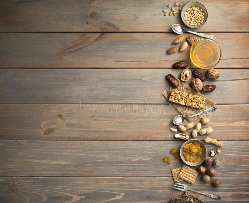 Nuts, dried fruits, honey and old spoons and forks on a old wooden table background. stock photo