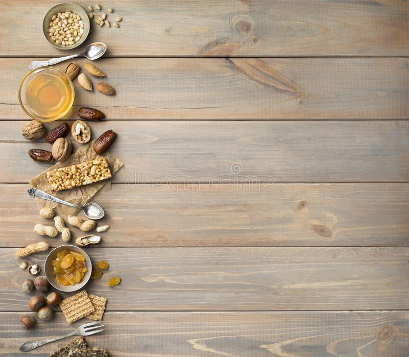Nuts, dried fruits, honey and old spoons and forks on a wooden table background. Copy spase.  royalty free stock images