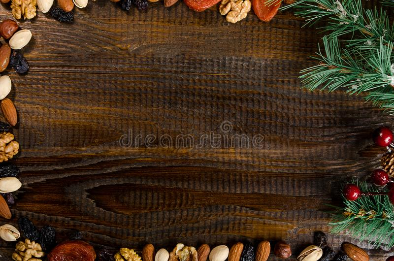 Nuts, dried fruits, pistachios and homemade cookies scattered from the bag on the table, New Year attributes, with a place for wri stock photos