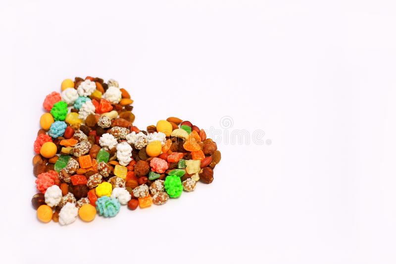 Nuts, dried fruits, sweets laid out in the shape of a heart on a white background stock photo