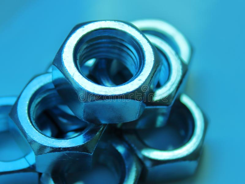 Nuts industrial abstraction close up blurred blue background stock image