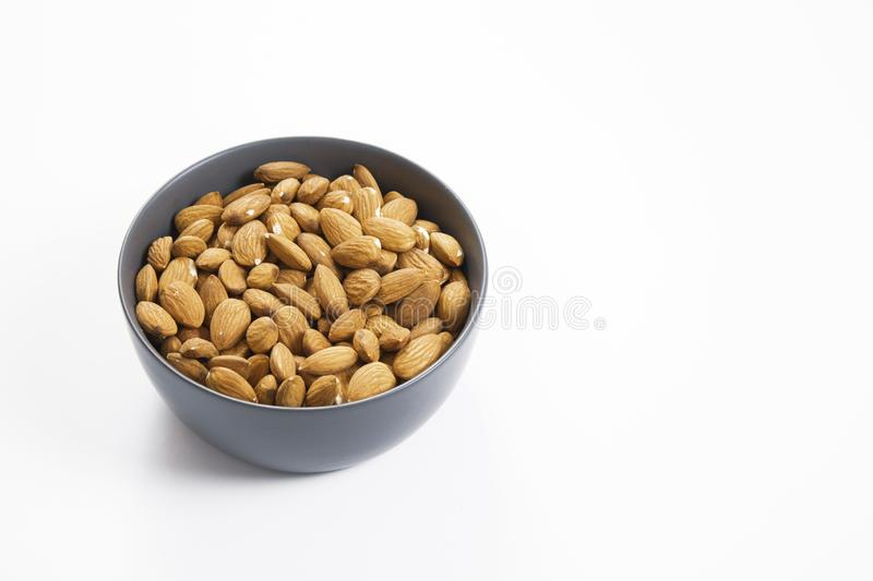 Almond nuts in bowl, isolated white background stock images
